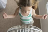 High angle view of girl standing in front of windy electric fan - CAVF55319