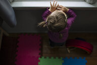 High angle view of baby girl looking through window while standing at home - CAVF55328
