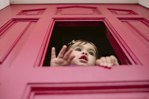 Low angle view of cute baby girl looking through window - CAVF55331