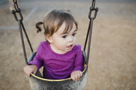 High angle view of cute baby girl looking away while sitting in swing at playground - CAVF55334
