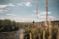 Young man fishing in lake while standing on grassy field against sky - CAVF55448