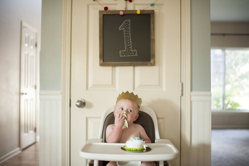 Baby boy eating cake while sitting on high chair at home during birthday - CAVF55454