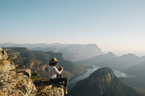 Side view of woman looking at view while sitting on mountain against clear sky - CAVF55466