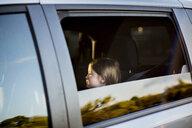 Girl sitting in car seen through window - CAVF55478