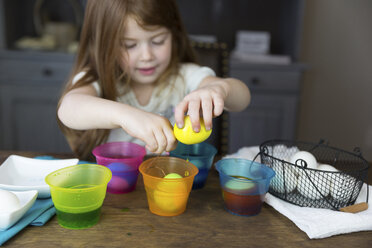 Girl coloring Easter Eggs on table at home - CAVF55484