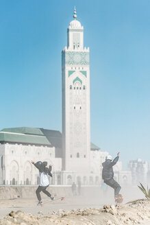 Full length of friends skateboarding against Mosque Hassan II - CAVF55493