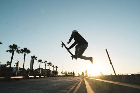 Side view of man performing stunt while skateboarding on road against sky - CAVF55496