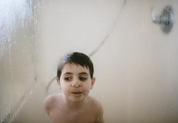 Shirtless boy pressing nose on condensed window in bathroom - CAVF55547
