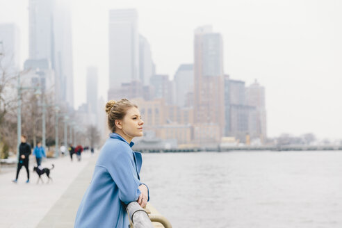 Confident young woman wearing trench coat while looking at river by railing against buildings in city - CAVF55556
