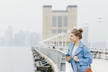 Confident young woman holding disposable cup while looking at river by railing in city - CAVF55559