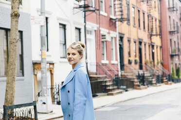 Portrait of confident young woman wearing trench coat while standing against residential buildings in city - CAVF55574