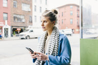 Young woman looking away while using smart phone in city - CAVF55580