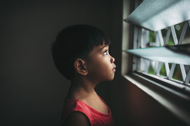 Side view of boy looking through window while standing at home - CAVF55583