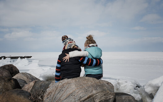 Rear view of siblings sitting on rock by frozen lake against cloudy sky - CAVF55601