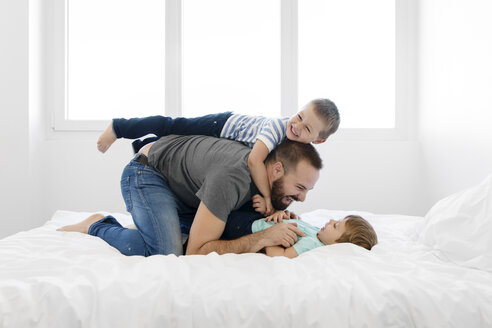 Playful father playing with sons on bed at home - CAVF55610