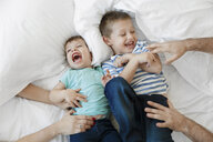Cropped hands of parents tickling sons on bed at home - CAVF55616