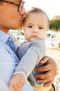 Portrait of cute daughter being kissed by father at beach - CAVF55625