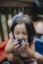 Girl with eyes closed eating blueberries on porch - CAVF55643