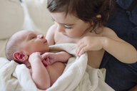 Sister looking at newborn brother by father at home - CAVF55724