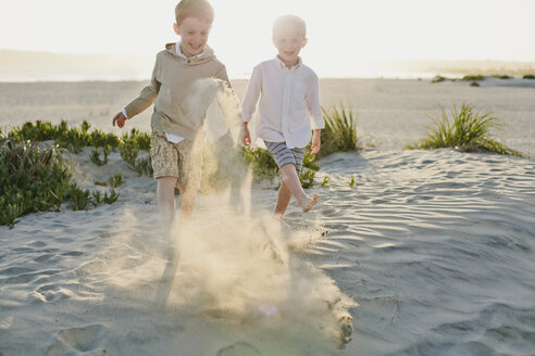 Playful brothers playing with sand at beach - CAVF55730