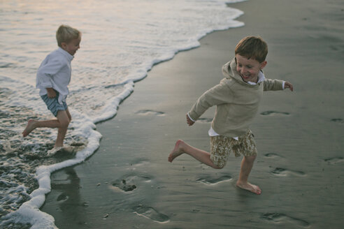 Side view of playful brothers running on shore at beach - CAVF55736