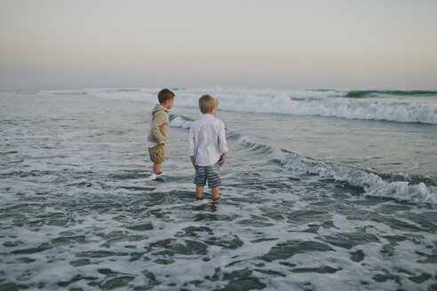 Carefree brothers standing in sea against clear sky during sunset - CAVF55742