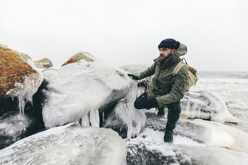Man crouching by frozen rocks at beach - CAVF55775