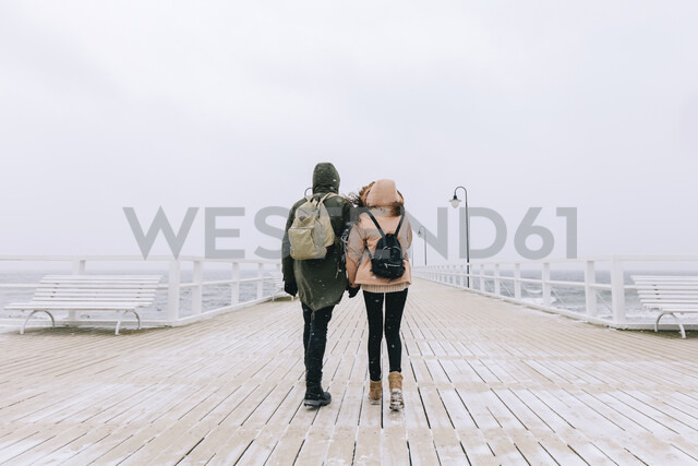 Rear view of couple with backpacks on pier against clear sky during winter - CAVF55778