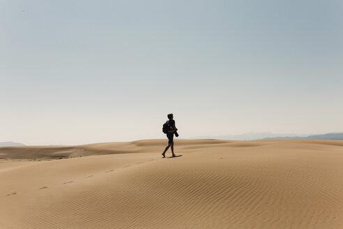 Full length of hiker with backpack exploring desert against sky - CAVF55799