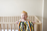 Baby boy crying while standing in crib against wall at home - CAVF55814