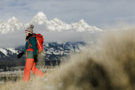 Side view of female hiker with backpack against snowcapped mountains - CAVF55829