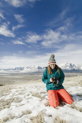 Female hiker looking at camera while kneeling on snowy field against mountains - CAVF55832