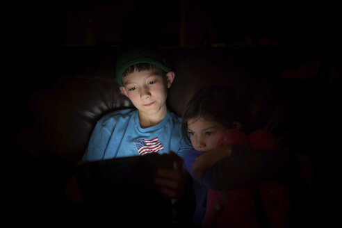 Siblings using tablet computer while sitting in darkroom at home - CAVF55850