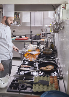 Chef holding flaming pan while preparing food at commercial kitchen - CAVF55856