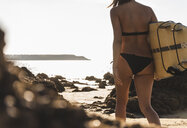 France, Brittany, young woman carrying surfboard on a rocky beach at the sea - UUF15882