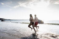 France, Brittany, young couple with surfboard running in the sea - UUF15903