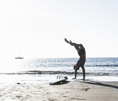France, Brittany, young man doing a handstand on the beach next to surfboard - UUF15915