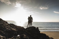 France, Brittany, rear view of young couple standing on rock at the beach at sunset - UUF15930