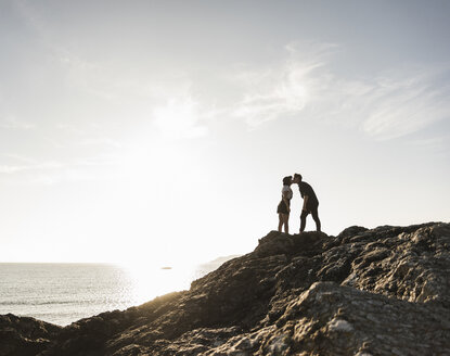 France, Brittany, young couple standing on rock at the beach at sunset kissing - UUF15933