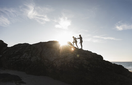 France, Brittany, young couple climbing on a rock at the beach at sunset - UUF15936