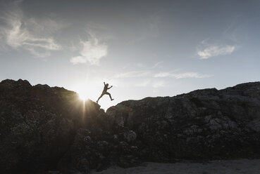 France, Brittany, young man jumping on a rock at sunset - UUF15939