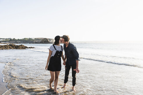 France, Brittany, young couple kissing at the beach - UUF15942