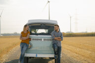 Happy couple at camper van in rural landscape with wind turbines in background - GUSF01391