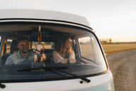Couple driving camper van on dirt track in rural landscape - GUSF01397