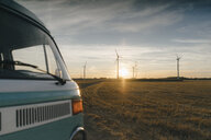 Camper van in rural landscape with wind turbines at sunset - GUSF01400