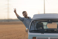 Excited young man making victory hand sign out of camper van window in rural landscape - GUSF01403
