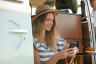 Smiling young woman using cell phone inside camper van - GUSF01406
