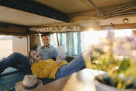 Happy young couple looking at tablet inside camper van - GUSF01409