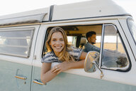 Portrait of happy woman leaning out of window of a camper van with man driving - GUSF01412