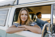 Portrait of smiling woman leaning out of window of a camper van with man driving - GUSF01421